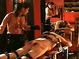 brunette woman into latex cloth hits tied up